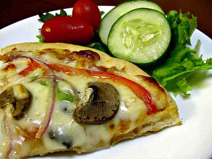 Mushrooms, Peppers And Red Onion Melt Into A Slice Of Cheesy Pizza Accompanied By Fresh Cucumbers And Tomatoes